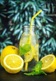 Citrinų limonado buteliukas su šiaudeliu stovi ant stalo-aplink guli perpjautos citrinos