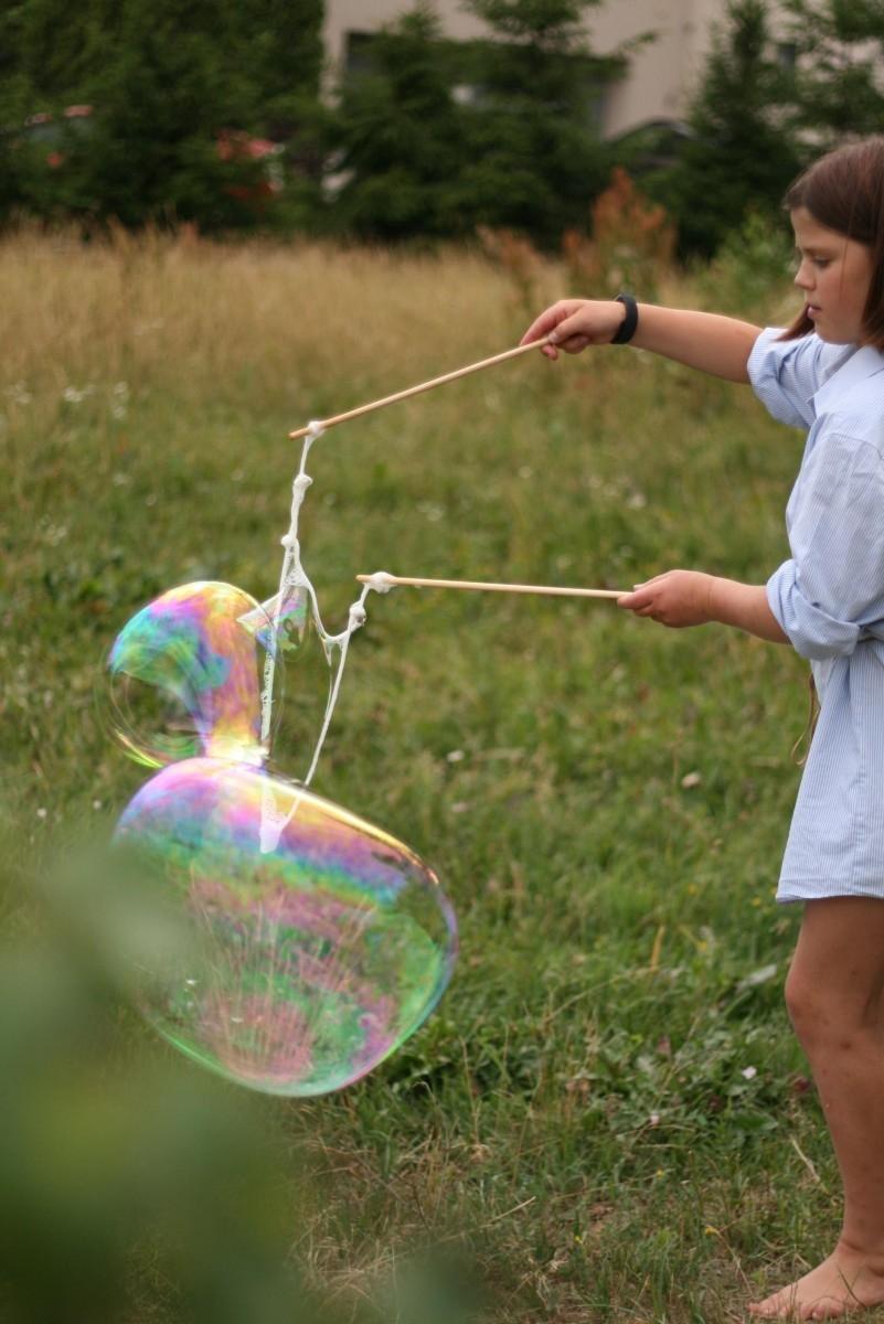 Dideli muilo burbulai virš pievos