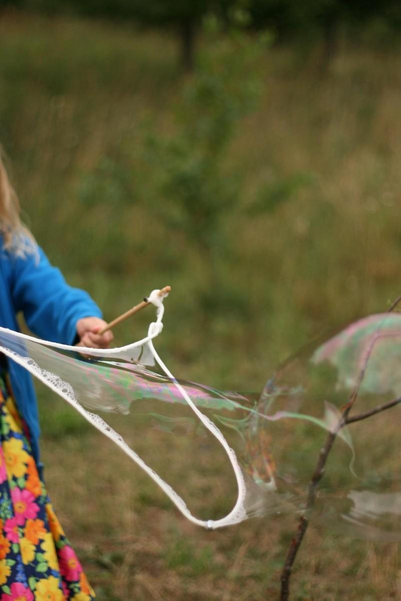 Mergaitės rankose lazdelės dideliems muilo burbulams pūsti