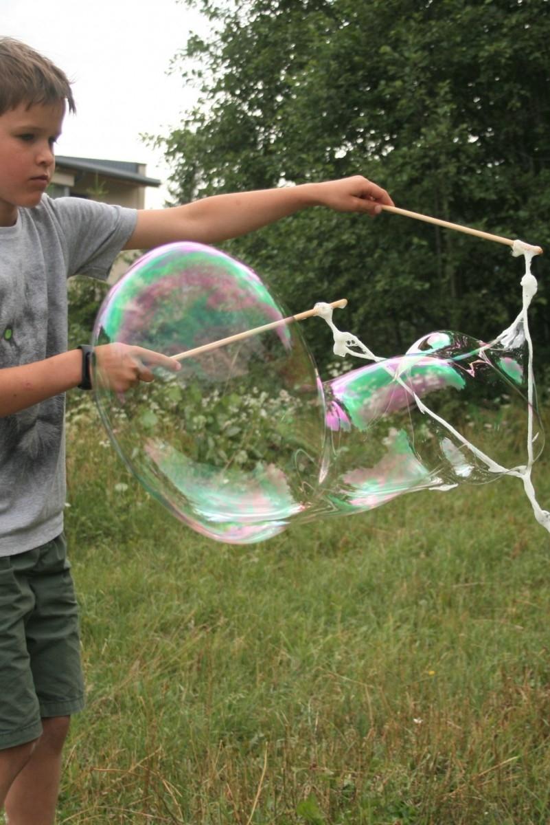 Berniukas pučia didelius muilo burbulus su lazdelėmis ir virve