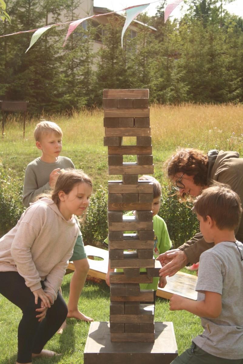 Žmonės žaidžia lauko žaidimą Jenga ir traukia kaladėlę iš bokšto