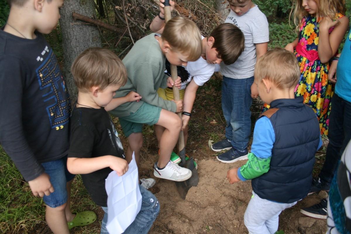Vaikai su kastuvu kasa lobio duobę