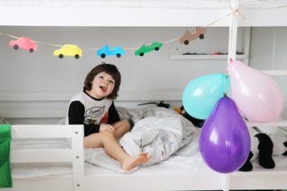 Vaikas žiūri į mašinytes lovoje balionai girlianda